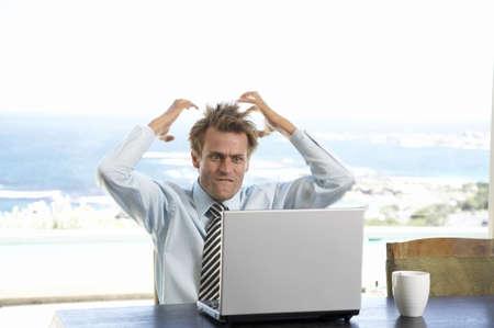 overstress: Man sitting at table, using laptop