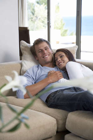 Couple relaxing on sofa Stock Photo - 23890945