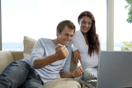 auction off: Couple sitting on couch, using laptop