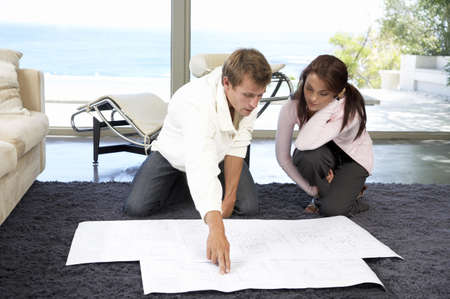 Couple in living room with construction plans Stock Photo - 23890949