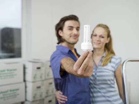 accrued: Couple embracing, man holding bulb
