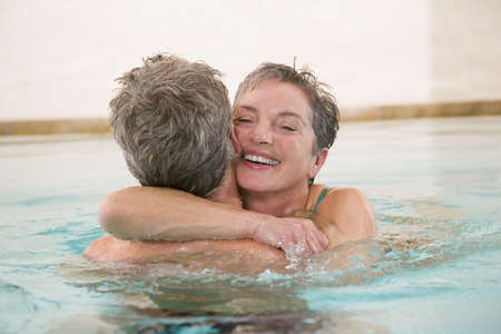 interiour shots: Mature couple embracing in swimmingpool, portrait