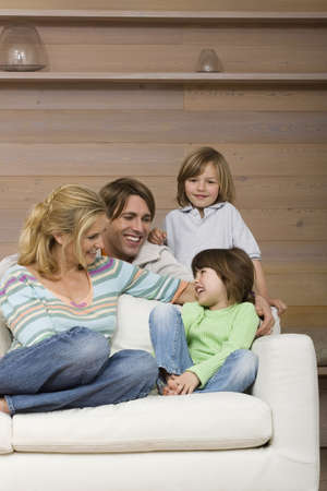 20 29: Family sitting on sofa, smiling, portrait