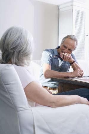 interiour shots: Senior couple sitting in living room, smiling, portrait LANG_EVOIMAGES