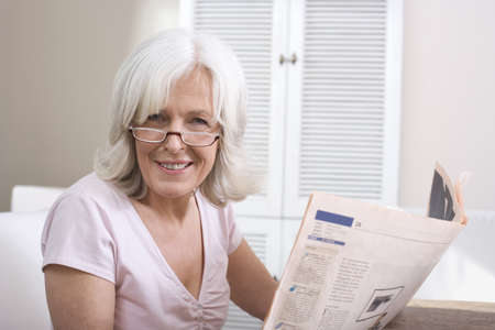 Senior woman holding newspaper, smiling, portrait Stock Photo - 23891007