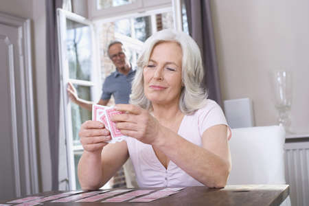 age 50 55 years: Senior woman playing Solitaire, senior man in background, portrait