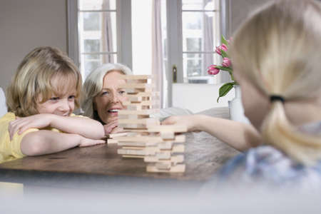 interiour shots: Grandmother and grandchildren (8-9) playing together