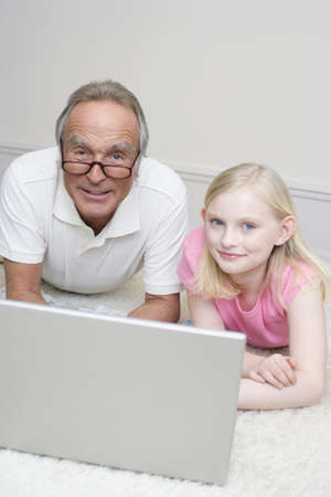 60 64 years: Grandfather and granddaughter (8-9) lying on floor, using laptop, portrait LANG_EVOIMAGES
