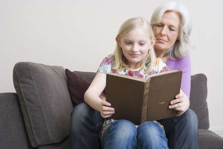 55 59 years: Grandmother and granddaughter (8-9) reading book on sofa, portrait