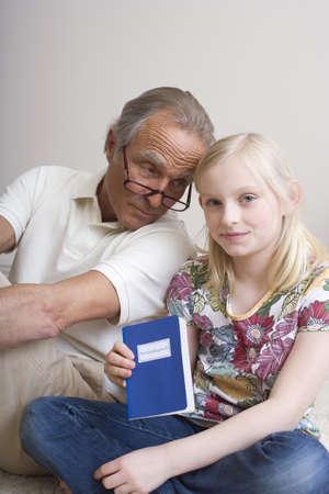 interiour shots: Granddaughter (8-9) holding bankbook, grandfather alongside, portrait LANG_EVOIMAGES