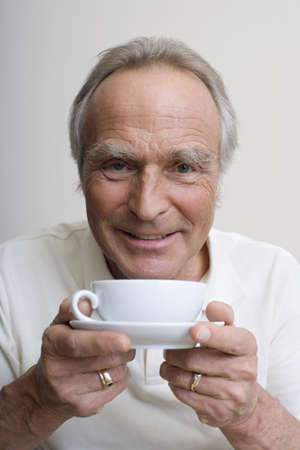 60 64 years: Senior man holding cup of coffee, portrait LANG_EVOIMAGES