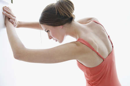 Young woman stretching against wall Stock Photo - 23891047