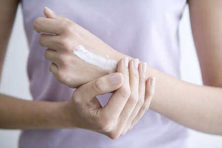 interiour shots: Woman applying cream to hands, close-up