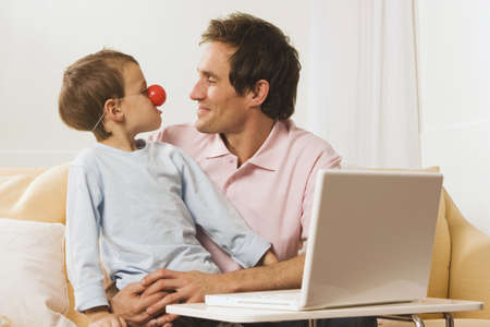 Father and son (4-5) at laptop, boy wearing clown nose Stock Photo - 23891053
