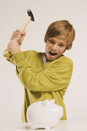 interiour shots: Teenage boy (13-14) brandishing hammer, piggy bank in foreground LANG_EVOIMAGES