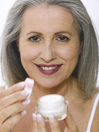 65 70 years: senior woman opening cream pot