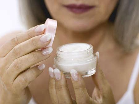 accrued: senior woman opening cream pot