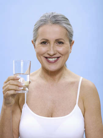 accrued: Senior woman holding glass of water, portrait LANG_EVOIMAGES