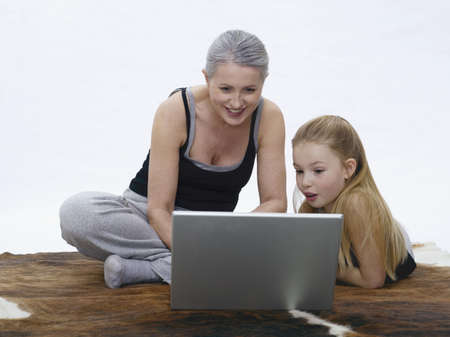 coherence: Grandmother and granddaughter using laptop, portrait LANG_EVOIMAGES