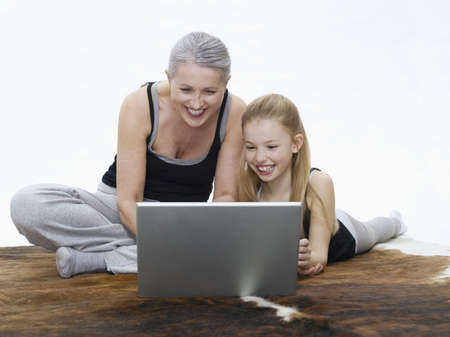 grizzled: Grandmother and granddaughter using laptop, portrait LANG_EVOIMAGES