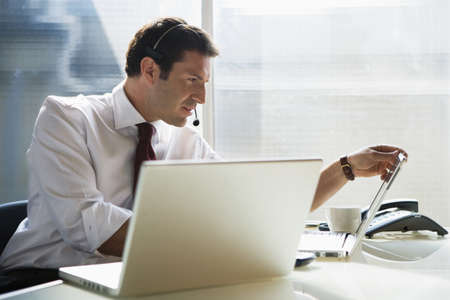 planned: Business man sitting at desk, using head set