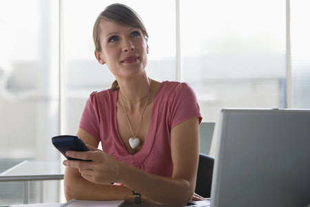 appointee: Business woman using a palmtop, sitting at desk