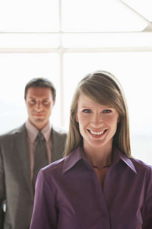 interiour shots: Two businesspeople, man and woman smiling LANG_EVOIMAGES