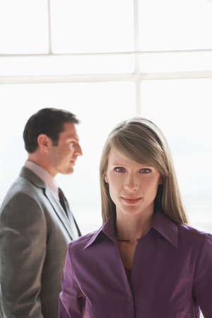 appointee: Portrait of business woman, male colleague in background