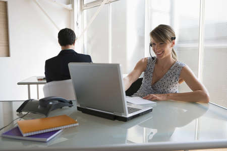 everyday jobs: Business woman with headset working on laptop, male colleague in background