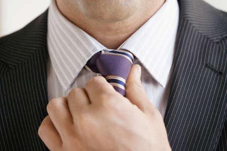 knotting: Business man adjusting tie, close up LANG_EVOIMAGES