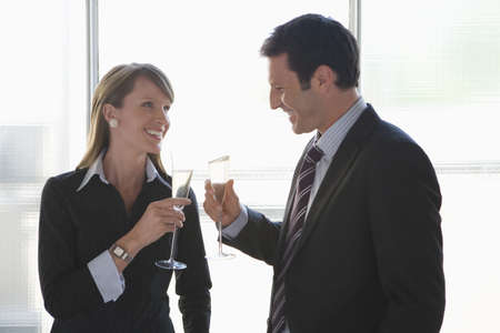 interiour shots: Business woman and business man toasting with sparkling wine