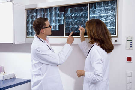diagnoses: Male doctor and a female doctor examining an x-ray report LANG_EVOIMAGES
