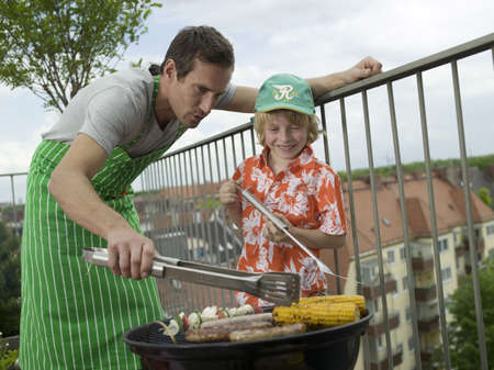 grill tongs sausage: Father and son preparing barbecue LANG_EVOIMAGES