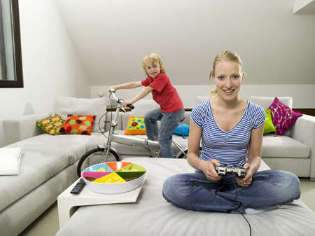 Mother and son in living room, mother playing computre game Stock Photo - 23891164