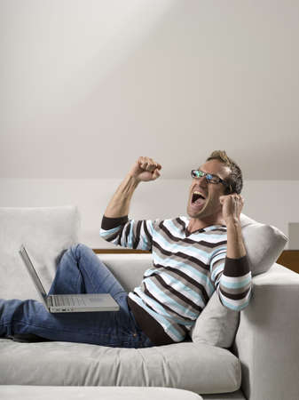 Man sitting on sofa, using laptop Stock Photo - 23891168