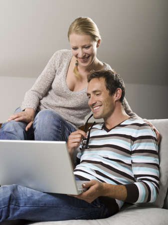 Couple sitting on sofa, using laptop Stock Photo - 23891169