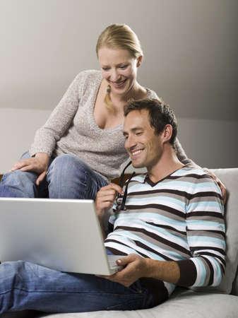 Couple sitting on sofa, using laptop Stock Photo - 23891169