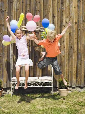 Boy and girl jumping, outdoors Stock Photo - 23891173