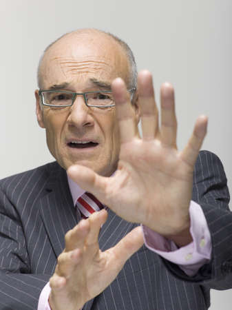 age 50 55 years: Senior businessman making a stop gesture, portrait