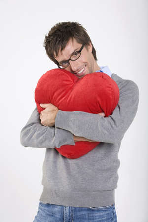 interiour shots: Young man holding heart-shaped cushion, smiling, portrait