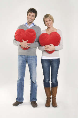 heartshaped: Young couple holding heart-shaped cushions, portrait LANG_EVOIMAGES