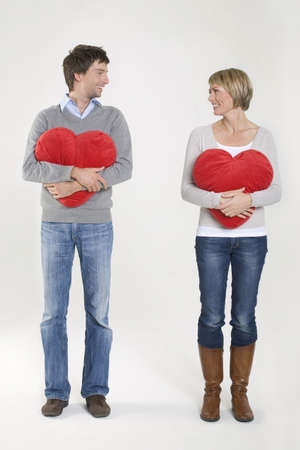 heartshaped: Young couple holding heart-shaped cushion, portrait