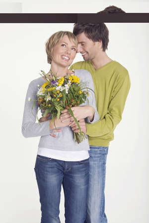interiour shots: Young man giving young woman bunch of flowers, portrait LANG_EVOIMAGES