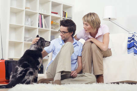 Couple in living room, with dog, portrait Stock Photo - 23891267