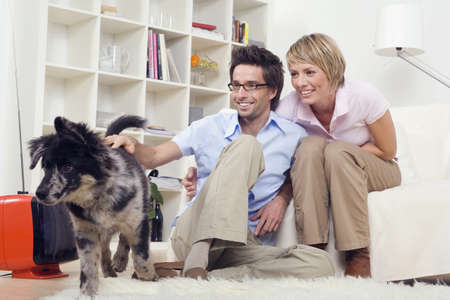 Couple in living room, with dog, portrait Stock Photo - 23891268