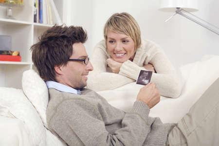 Couple, Man looking at ultrasound photos Stock Photo - 23891269