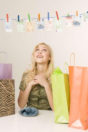 interiour shots: Blonde woman drying money on a clothesline, portrait LANG_EVOIMAGES
