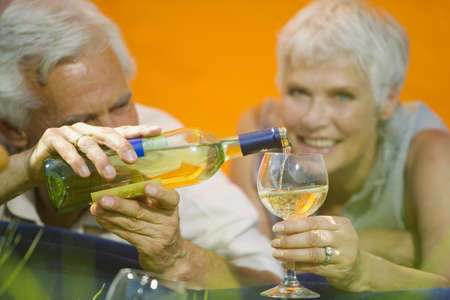 60 64 years: Senior couple drinking white wine, portrait