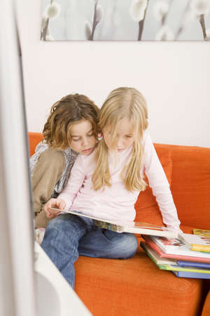 Brother and sister reading a book together Stock Photo - 23891331