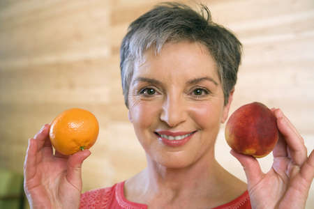 Mature woman holding fruits, smiling, portrait Stock Photo - 23891361